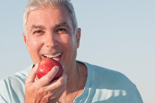 השתלת שיניים גבר אוכל תפוח